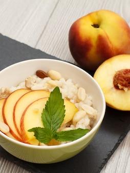 수수 죽, 신선한 복숭아, 캐슈 너트, 아몬드, 민트 잎을 돌판과 회색 나무 배경에 넣은 도자기 그릇. 신선한 과일을 곁들인 비건 글루텐 프리 수수 샐러드. 평면도.