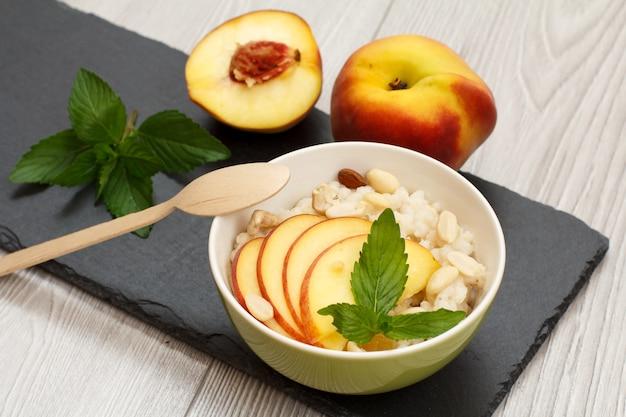 수수 죽, 신선한 복숭아, 캐슈 너트, 아몬드, 민트 잎이 있는 도자기 그릇, 돌판과 회색 탁자에 있는 나무 숟가락. 신선한 과일을 곁들인 비건 글루텐 프리 수수 샐러드. 평면도.