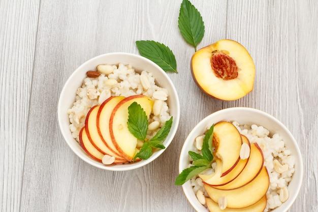 회색 나무 판자에 수수 죽, 자른 복숭아, 캐슈넛, 아몬드, 민트 잎이 있는 도자기 그릇. 신선한 과일을 곁들인 비건 글루텐 프리 수수 샐러드. 평면도.