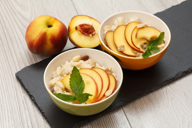 수수 죽, 신선한 복숭아, 캐슈넛, 아몬드, 민트 잎을 검은 돌판에 얹은 도자기 그릇. 신선한 과일을 곁들인 비건 글루텐 프리 수수 샐러드. 평면도.