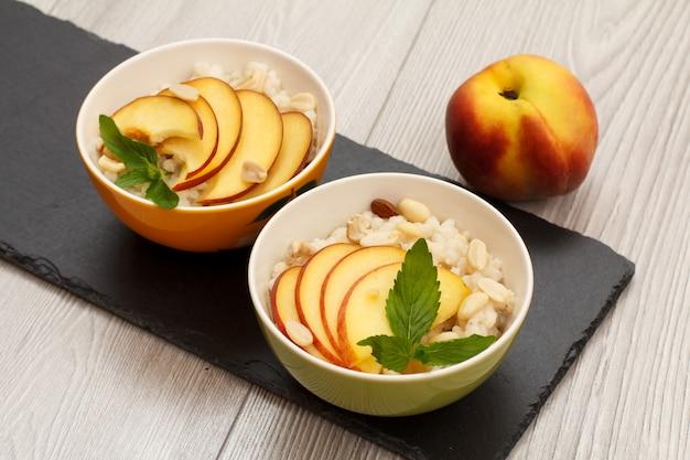 수수 죽, 복숭아, 캐슈넛, 아몬드, 민트 잎을 검은 돌판에 얹은 도자기 그릇. 신선한 과일을 곁들인 비건 글루텐 프리 수수 샐러드. 평면도.