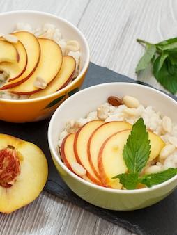 돌판에 수수 죽, 복숭아, 캐슈넛, 아몬드, 민트 잎을 넣은 도자기 그릇. 신선한 과일을 곁들인 비건 글루텐 프리 수수 샐러드. 평면도.