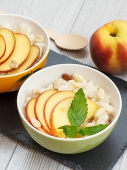 수수 죽, 복숭아, 캐슈 너트, 아몬드, 민트 잎이 있는 도자기 그릇, 검은 돌판에 나무 숟가락. 신선한 과일을 곁들인 비건 글루텐 프리 수수 샐러드. 평면도.