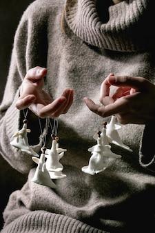 도자기 크리스마스 천사. 양모 풀오버를 입은 여성은 흰색 공예품 크리스마스 천사 장식 세트를 손가락으로 잡고 있습니다. 어두운 배경입니다.