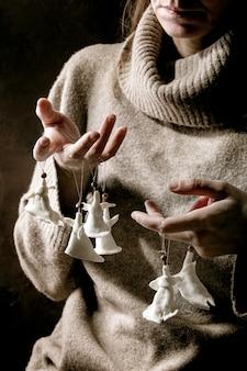 磁器のクリスマスの天使。ウールのプルオーバーの女性は、白い工芸品の手作りのクリスマスの天使の装飾の指のセットを保持します。