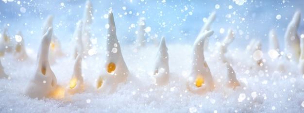 도자기 크리스마스 집입니다. 반짝이는 눈 위에 빛나는 창문이 있는 수제 크리스마스 장식 집 세트. 배너 크기