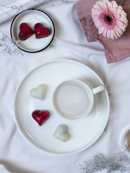Фарфоровая чашка кофе с кремом и вкусные конфеты с форме сердца на белой кровати. доброе утро концепция. плоская планировка, вид сверху, вертикальное изображение