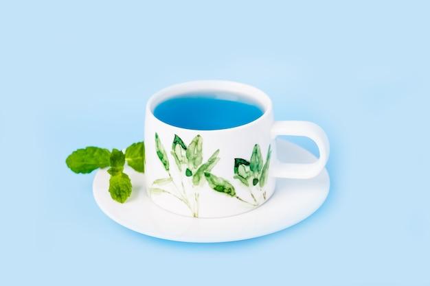 ミントの葉と有機ブルーバタフライエンドウ豆フラワーティーの磁器カップ