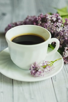 Porcelain cup with coffee and lilac