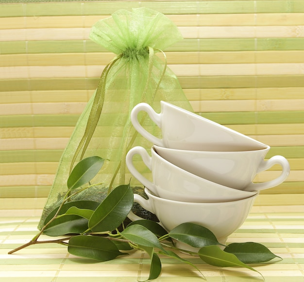 Porcelain cups, green leaves and a bag of tea on the background of a striped mat