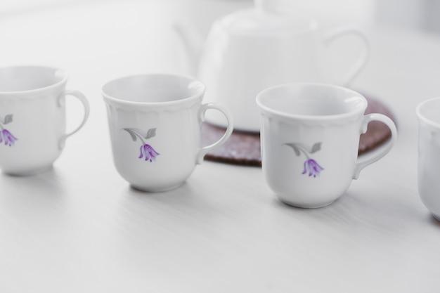 Фарфоровые чашки возле чайника