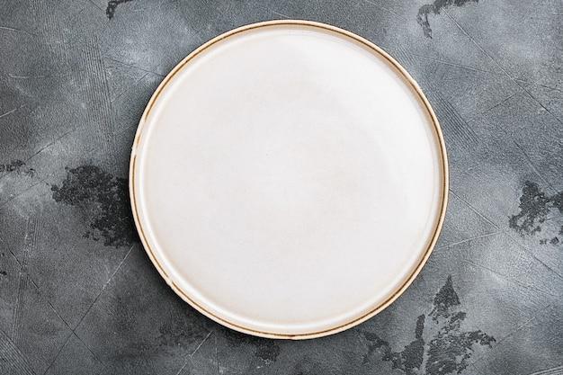 텍스트 또는 음식을 위한 복사 공간이 있는 도자기 빈 흰색 접시 세트, 회색 석재 테이블 배경 위에 있는 위쪽 보기 플랫