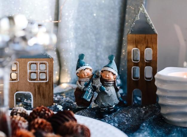크리스마스 장식에 어린이의 도자기 인형. 집과 콘의 배경에 선물을 가진 소년과 소녀의 겨울 인형. 크리스마스 인사말 카드입니다. 공간을 복사합니다.