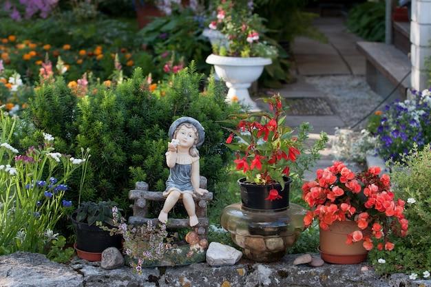 裸足でベンチの庭に座って、赤い花が付いている鍋の周りに、さまざまな植物を育てる磁器の庭の置物のおもちゃの女の子