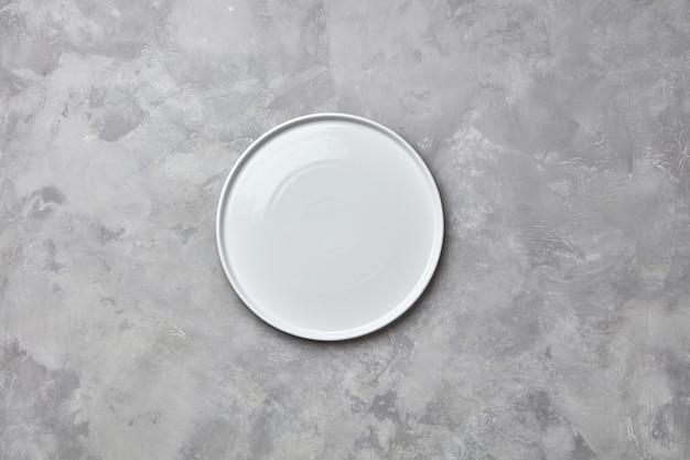 회색 콘크리트 테이블에 도자기 수제 빈 둥근 접시