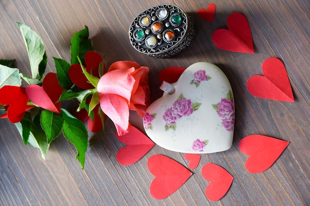 Porcelain heart on the wood table with flower and paper heart.