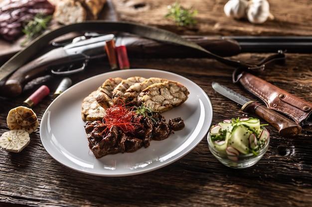 鹿肉のグーラッシュシチューがたっぷり入った磁器プレートに、餃子と新鮮なサラダを前菜として添えて。食べ物は、ハンティングショットガン、弾丸、素朴なナイフなどのハンティングアクセサリーに囲まれています。 Premium写真