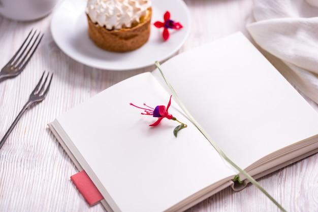磁器プレート、ケーキ、開いたレシピ本、ノート、本