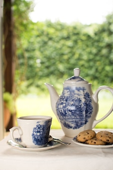 Porcelain teapot and teacups with whale shaped cookie on table at outdoors