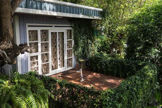 エクササイズ機器と植物の装飾が施されたポーチバルコニーベランダ。緑のライフスタイルコンセプトと家の外観。