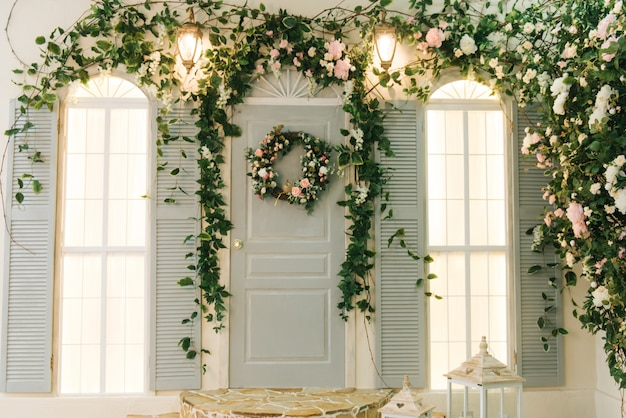 The porch of the house with windows is decorated with beautiful green flowers, spring decor