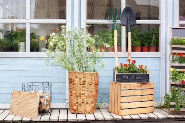 식물과 꽃이있는 집 현관 정원 도구가있는 집 외관 아늑한 여름 장식 베란다 집