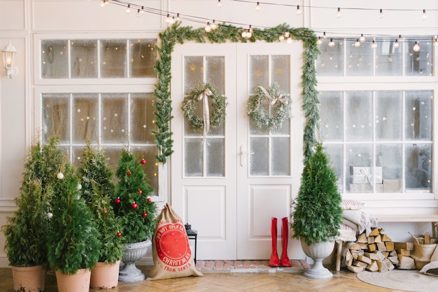 Крыльцо с белой дверью в елочных украшениях и елках.