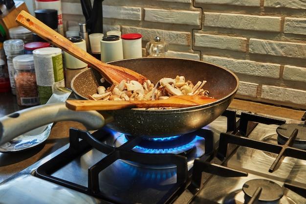 Белые грибы и шампиньоны обжариваются на сильном огне на газовой плите.