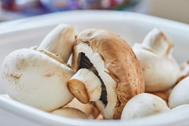 Белые грибы и шампиньоны в тарелке готовы к нарезке.