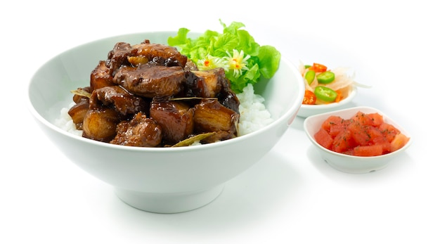 Pork adobo caramelised on rice recipe filipino dish added with the sweet and sour taste popular dish in the philippines asean foods served inside dish and vegetables sideview