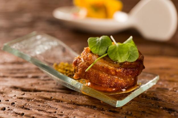 Салат из свинины с пурурукой, водяной мукой, тыквенным пюре и проростками в ложке. вкус гастрономической еды руками
