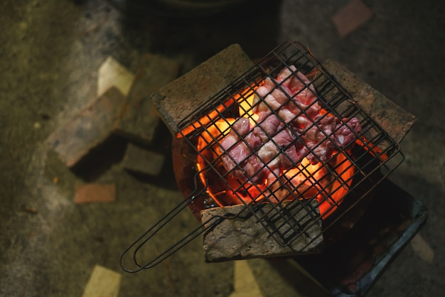 Pork barbecue over burned red hot charcoal