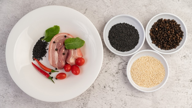豚バラ肉をコショウの種とトマトの白い皿にスライスしました。