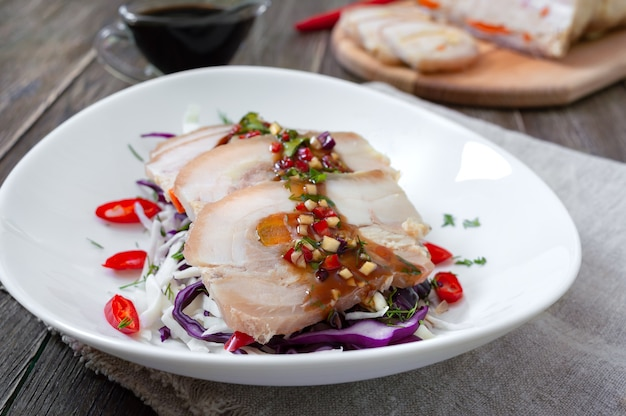 Pork belly with cabbage salad in a white bowl on a wooden background. chinese cuisine.