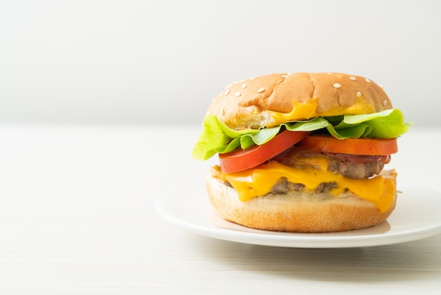 Pork burger with cheese on white plate