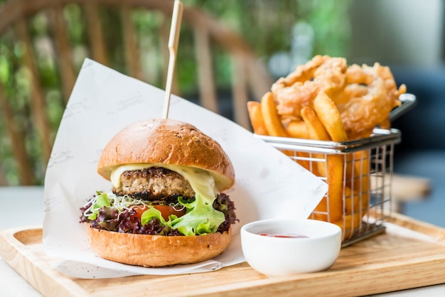 Pork burger with onion rings and french fries