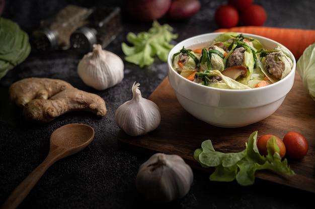 にんじん、みじん切りねぎ、きゅうりの入った豚肉のキャベツスープ