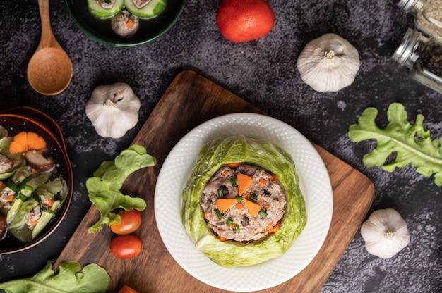Щи из свинины с морковью, нарезанным зеленым луком, огурцом в деревянной тарелке на деревянной тарелке