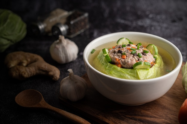 Pork cabbage soup with carrots, chopped green onions, cucumber in a wooden plate on a wooden plate