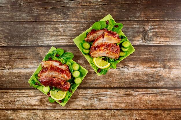 Отбивная из свинины, запеченная с соусом барбекю, огурцом и шпинатом.