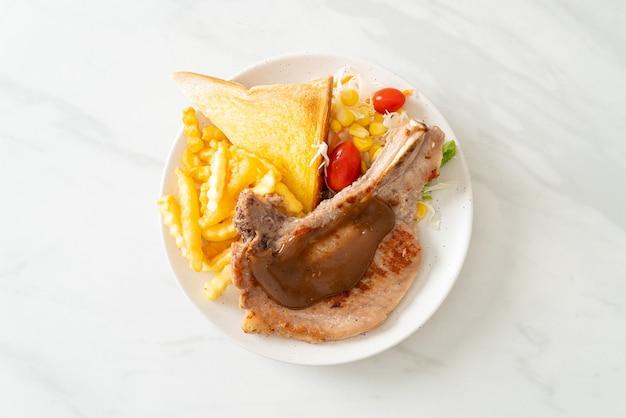 Стейк из свиной отбивной с чипсами и мини-салатом на белой тарелке
