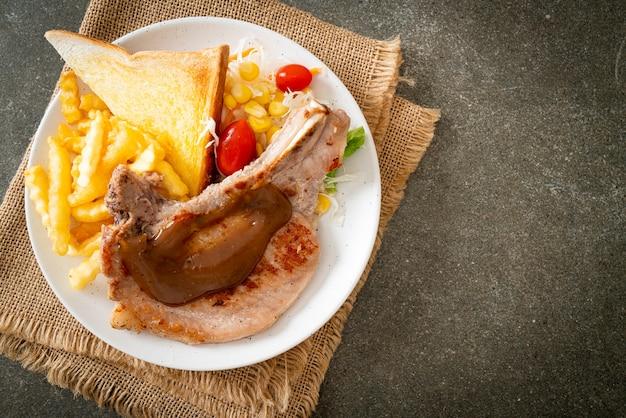 Стейк из свиной отбивной с чипсами и мини-салатом на белой тарелке Premium Фотографии