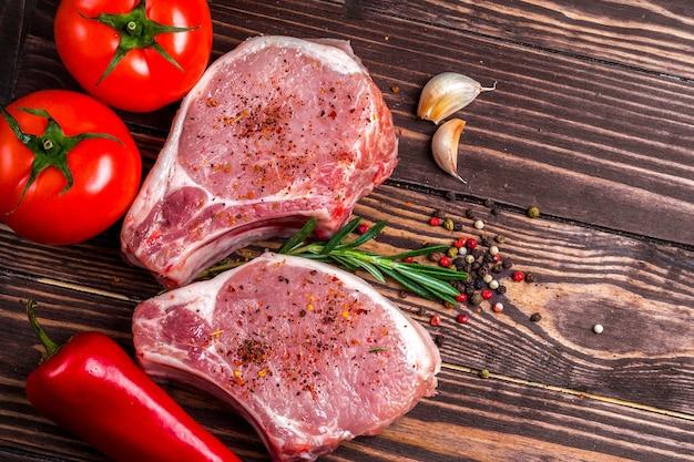 ポークチョップステーキと野菜とスパイスの上面図。生肉、トマト、赤唐辛子、ピーマン