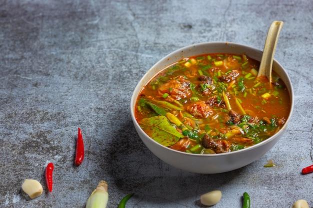 Curry di maiale, cucina tailandese su fondo di legno.