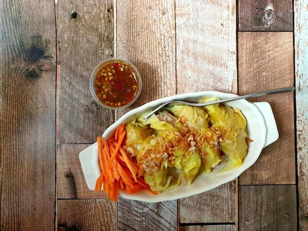 ポーク餃子にんにくの揚げニンニクとにんじんのスライスをクレードルボウルに入れ、木製のテーブルにソースをかける