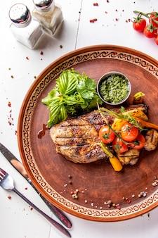 豚肉のアントレコートグリル野菜、マッシュルーム、ペストソース添え、レストランの料理、上面図、縦向き
