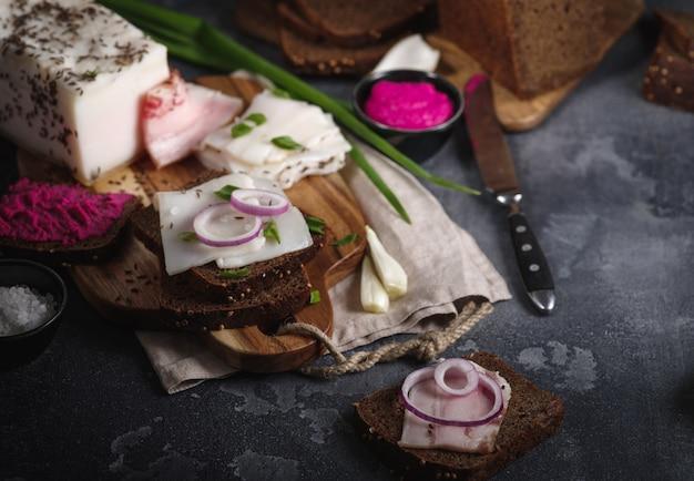 Pork fatback sandwich with onion on wooden board.