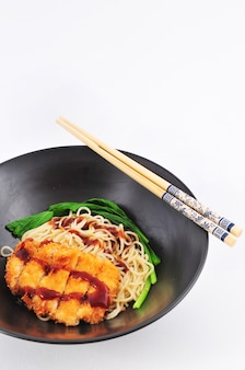 Pork fritter noodle topped with japanese sauce on white background