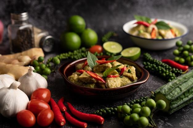Curry di maiale verde in una ciotola marrone con spezie su uno sfondo di cemento nero
