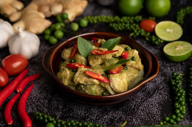 Pork green curry in a brown bowl with spices on a black cement background